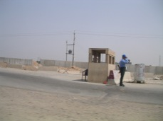 We drive past a lone Iraqi policeman at his checkpoint. When an Iraqi police man or soldier was posted in the middle of the road, by themselves, we would refer to those positions as suicide posts. Here the Iraqi policeman is not wearing a mask or baclava indicating the area was somewhat controlled and sympathetic to Iraqi government and coalition forces.